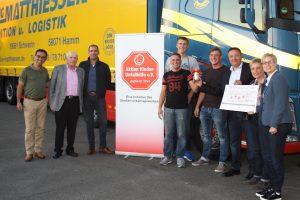 Nils Hüttenrauch von der SVG Consult (weißes Hemd) erhielt den Scheck aus den Händen der Familie Matthiessen und der Mitarbeiter der Spedition.